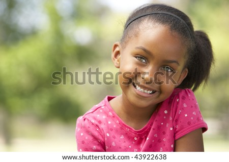 Portrait Of Young Girl Sitting In Park - stock photo