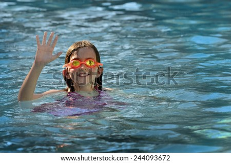Portrait of young girl swimming with orange swim goggles in pool - stock photo
