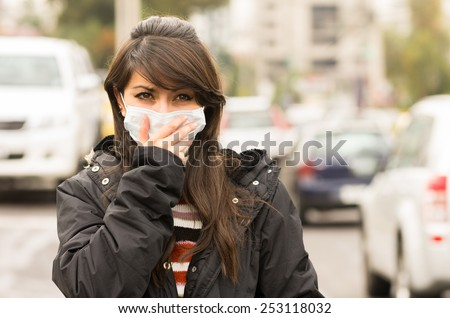 portrait of young girl walking wearing a mask in the city street concept of  pollution - stock photo