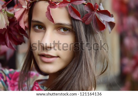 Portrait of young girl with autumn foliage - stock photo