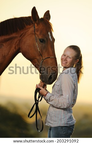 Portrait of  young  girl with chestnut horse  at the sunset  - stock photo