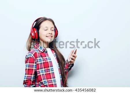 Portrait of young girl with headphones on grey background - stock photo