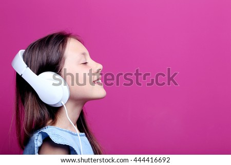 Portrait of young girl with headphones on pink background - stock photo