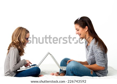 Portrait of Young Girls working together on laptops.Isolated on white background. - stock photo