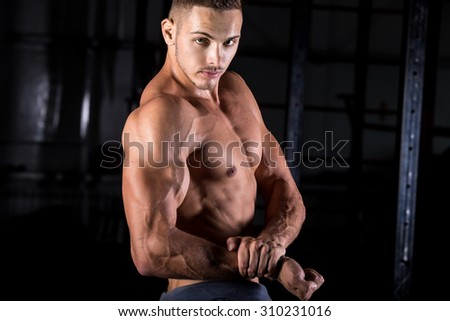 Portrait of young good looking caucasian muscular man working out in gym, posing, showing big biceps, chest muscles - stock photo