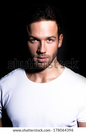 portrait of young good looking man staring at viewer against black background
