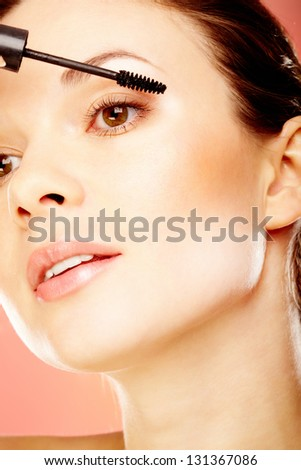 Portrait of young gorgeous female doing eye makeup