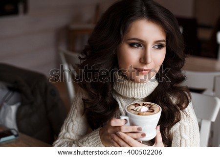 Portrait of young gorgeous woman drinking tea and looking thoughtfully out the window of the cafe, enjoying her leisure time, nice business women lunch at the cafe in their spare time - stock photo