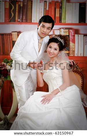 Portrait of young groom and bride in elegant dress - stock photo