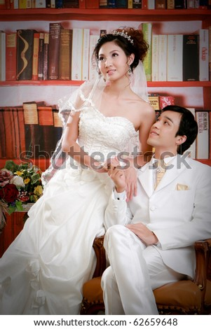 Portrait of young groom sitting and looking to his bride with romantic emotion - stock photo
