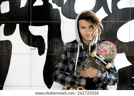 portrait of young guy  with skate and rasta hair in a lifestyle concept - stock photo