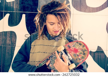 portrait of young guy  with skate and rasta hair in a lifestyle concept warm filter applied - stock photo