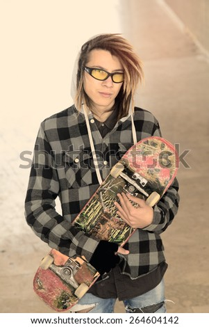 portrait of young guy  with skateboard and rasta hair in a lifestyle concept warm filter applied - stock photo