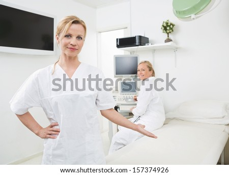 Portrait of young gynecologist gesturing with colleague using ultrasound machine in background at clinic - stock photo