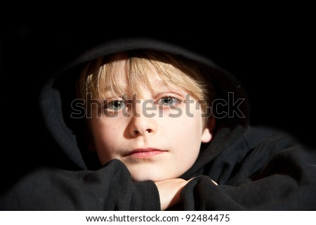 Portrait of young handscome boy on black background wearing black hooded top - stock photo