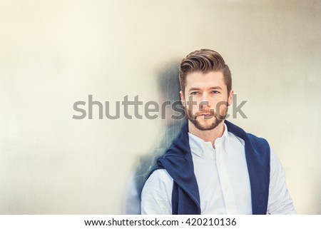 Portrait of Young Handsome American Man. Wearing white shirt, blue sweater putted around shoulder, a guy with beard standing against silver metal wall, seriously thinking, sad, lost in thought.  - stock photo