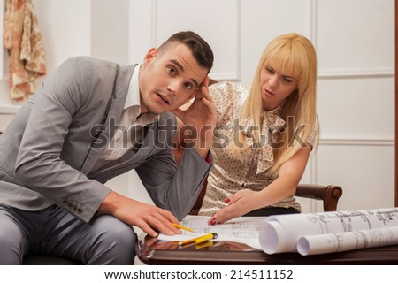 Portrait of young handsome architect discussing and arguing about ground plan with beautiful blonde woman client sitting at the table in design studio - stock photo