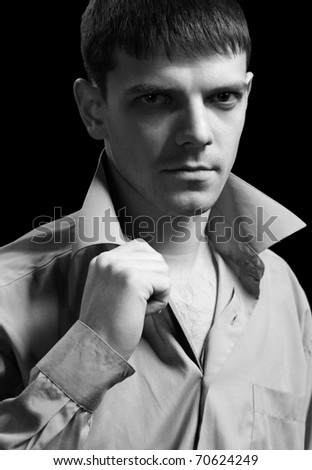 portrait of young handsome brunet guy in gray shirt checking collar on green - stock photo