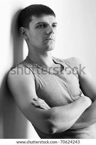 portrait of young handsome brunet guy in undershirt and jeans posing on gray