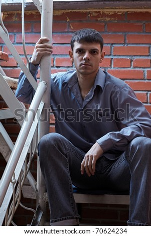 portrait of young handsome brunet guy posing near red brick wall
