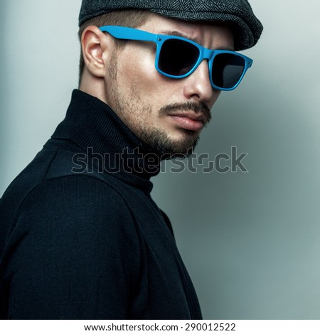 Portrait of young handsome brutal bearded man in blue sunglasses, cap, roll neck jumper. - stock photo
