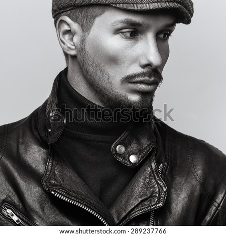 Portrait of young handsome brutal bearded man in leather jacket and in cap. - stock photo