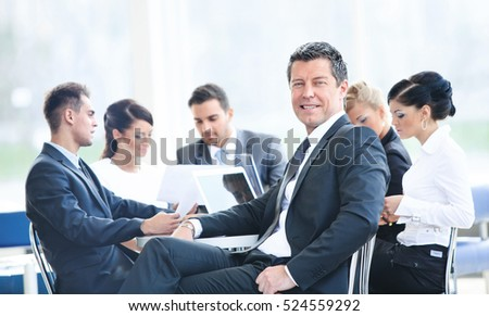 Portrait of young handsome businessman in office with colleagues in the background
