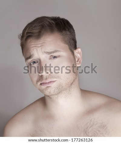 Portrait of young handsome calm man looking at camera. Studio shot. - stock photo