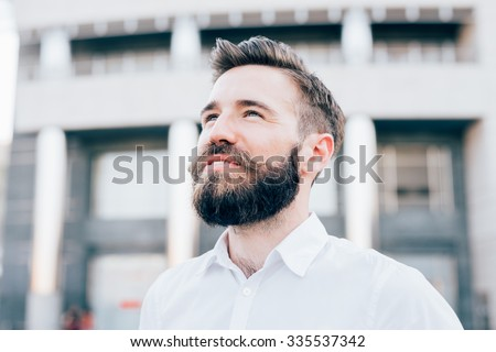Portrait of young handsome caucasian blonde modern businessman posing in the city backlight, overlooking right, smiling - successful, business concept - stock photo