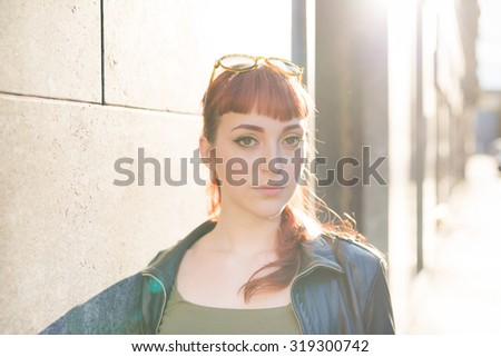 portrait of young handsome caucasian redhead woman leaning against a wall, looking in camera, serious - pensive concept - wearing leather jacket and green shirt - backlight - stock photo
