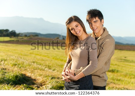 Portrait of young handsome couple in sunny countryside. - stock photo