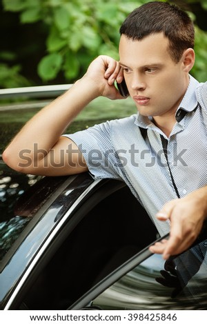 Portrait of young handsome dark-haired man about car speaking on mobile phone. - stock photo