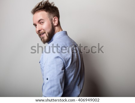 Portrait of young handsome friendly man in blue shirt. Studio photo on light grey background. - stock photo