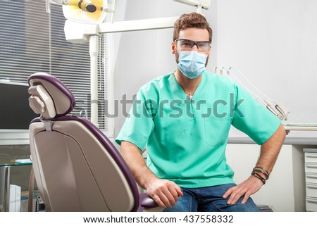 Portrait of young handsome male doctor in green costume wearing medical mask and glasses sitting in dentist chair in dental clinic. Face expressions, emotion, health care, medicine. - stock photo