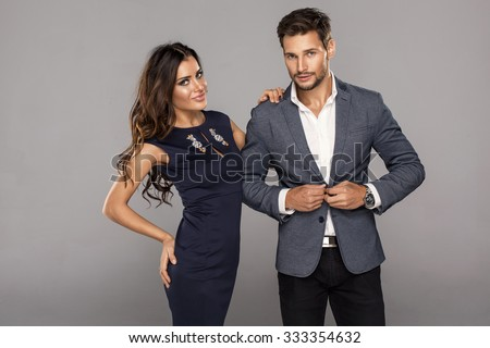 Portrait of young handsome man buttoning jacket with beautiful young woman. Beautiful couple in fashionable clothes - stock photo