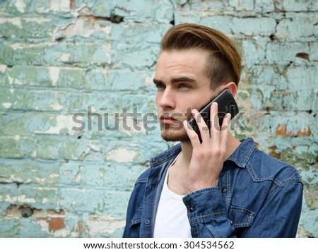 Portrait of young handsome man calling phone outdoor against grunge obsolete wall - stock photo