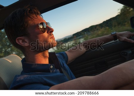 Portrait of young handsome man driving a car - stock photo