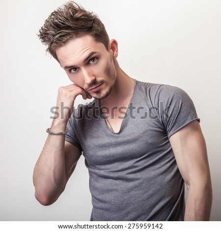 Portrait of young handsome man in grey t-shirt. - stock photo