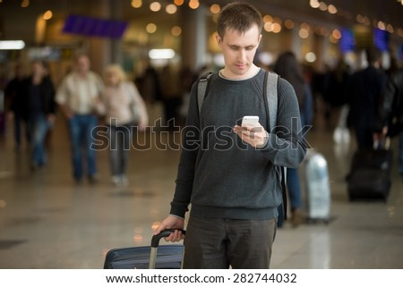 Portrait of young handsome man in 20s walking in modern airport terminal, using smart phone app in public wifi area, texting, travelling with luggage bag, wearing casual style clothes - stock photo