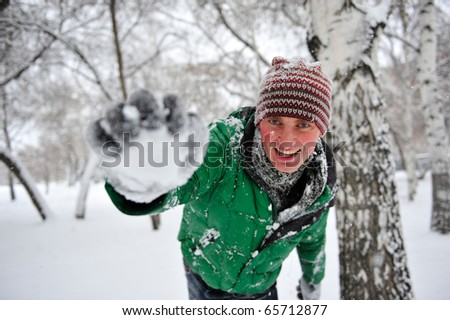 Portrait of young handsome man playing snowballs in winter park near tree wearing sportswear