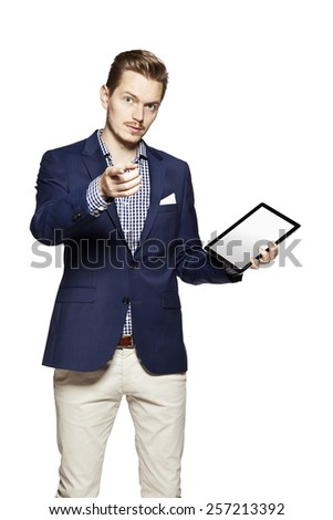 Portrait of young handsome man pointing at you and holding a digital tablet. - stock photo