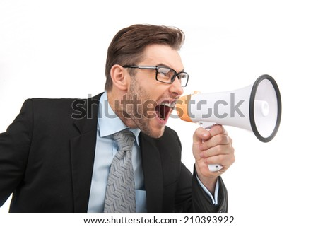 portrait of young handsome man shouting using megaphone. image of angry boss screaming on white background - stock photo