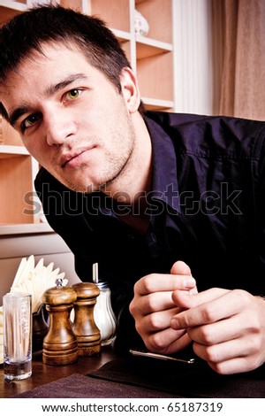 Portrait of young, handsome man thinking and waiting for woman in cafe