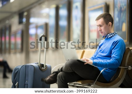 Portrait of young handsome man wearing casual style clothes sitting on the bench in modern airport using laptop. Passenger travelling with bag working with computer while waiting for transport - stock photo