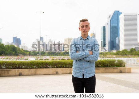 Portrait of young handsome man with blond hair relaxing at the park in the city of Bangkok, Thailand