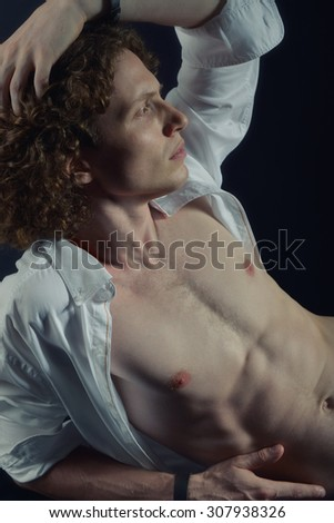 Portrait of young handsome man with open white shirt and rich curly hair over black background. Image toned and noise added. - stock photo
