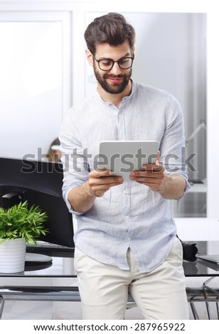 Portrait of young handsome sales man sitting at office desk in front of computer while holding digital tablet and touch the screen.  - stock photo
