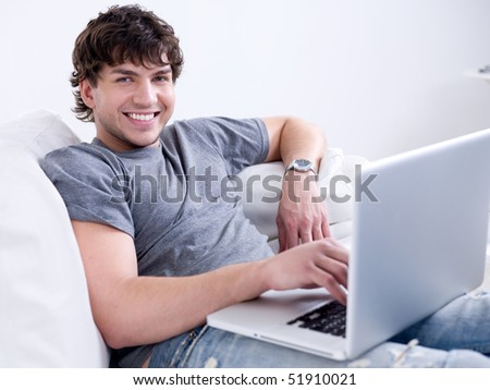Portrait of young handsome smiling man working on the laptop at home - stock photo