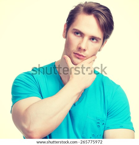 Portrait of young handsome thinking man in a blue shirt  -  isolated on white. - stock photo
