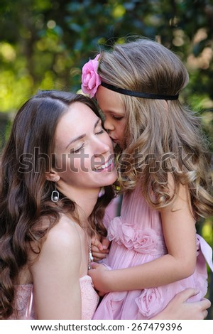 portrait of Young happy beautiful mother and daughter love and kiss at sun day outdoor - stock photo